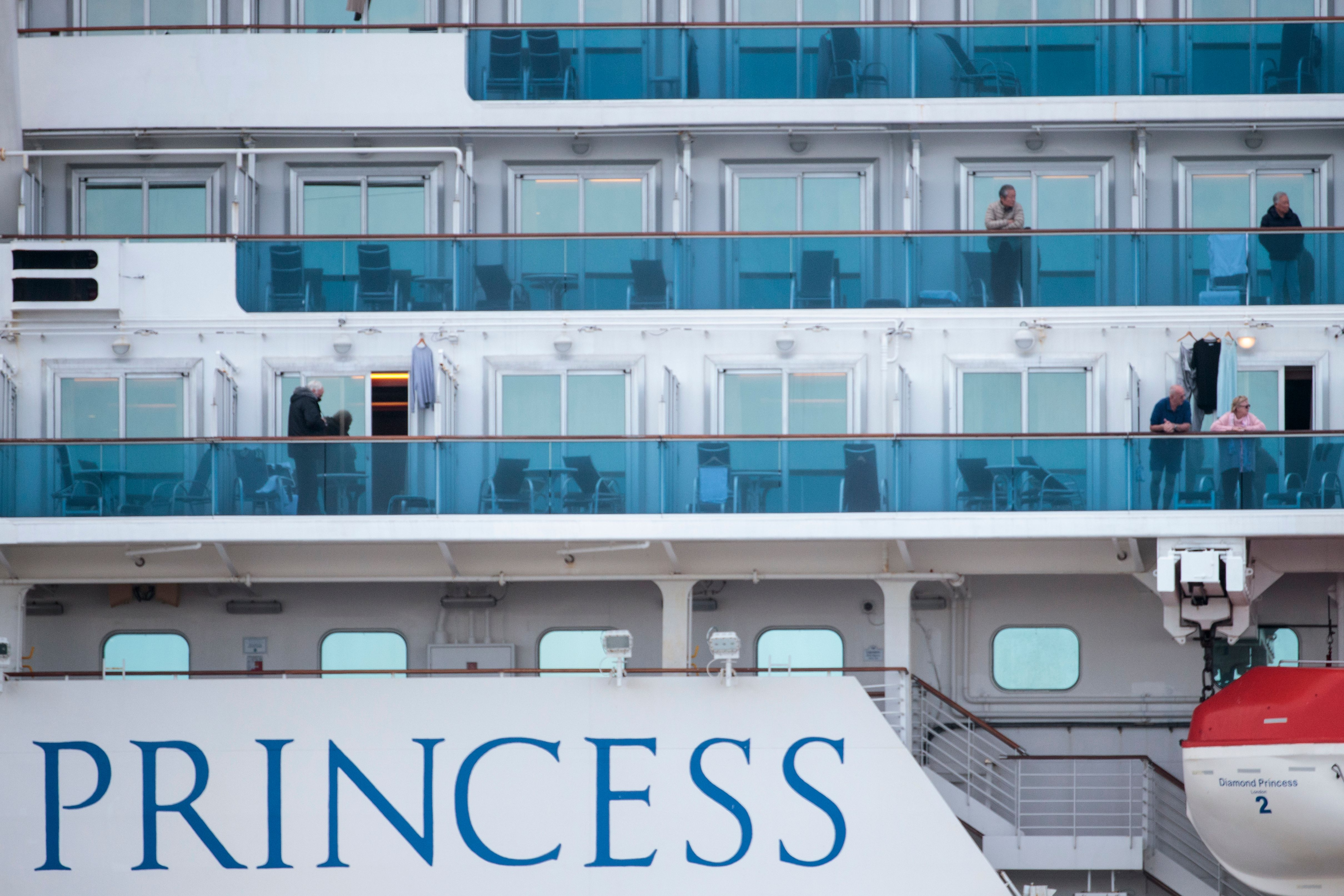 Passengers wearing face masks on the Diamond Princess cruise ship, docked in Yokohama, Japan on February 12, 2020.