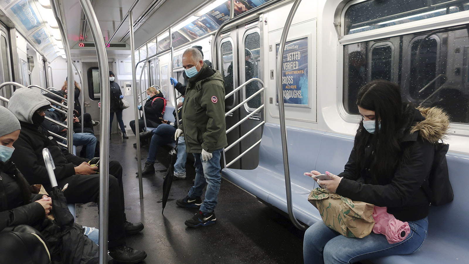 People in face masks ride the subway in New York on April 13.