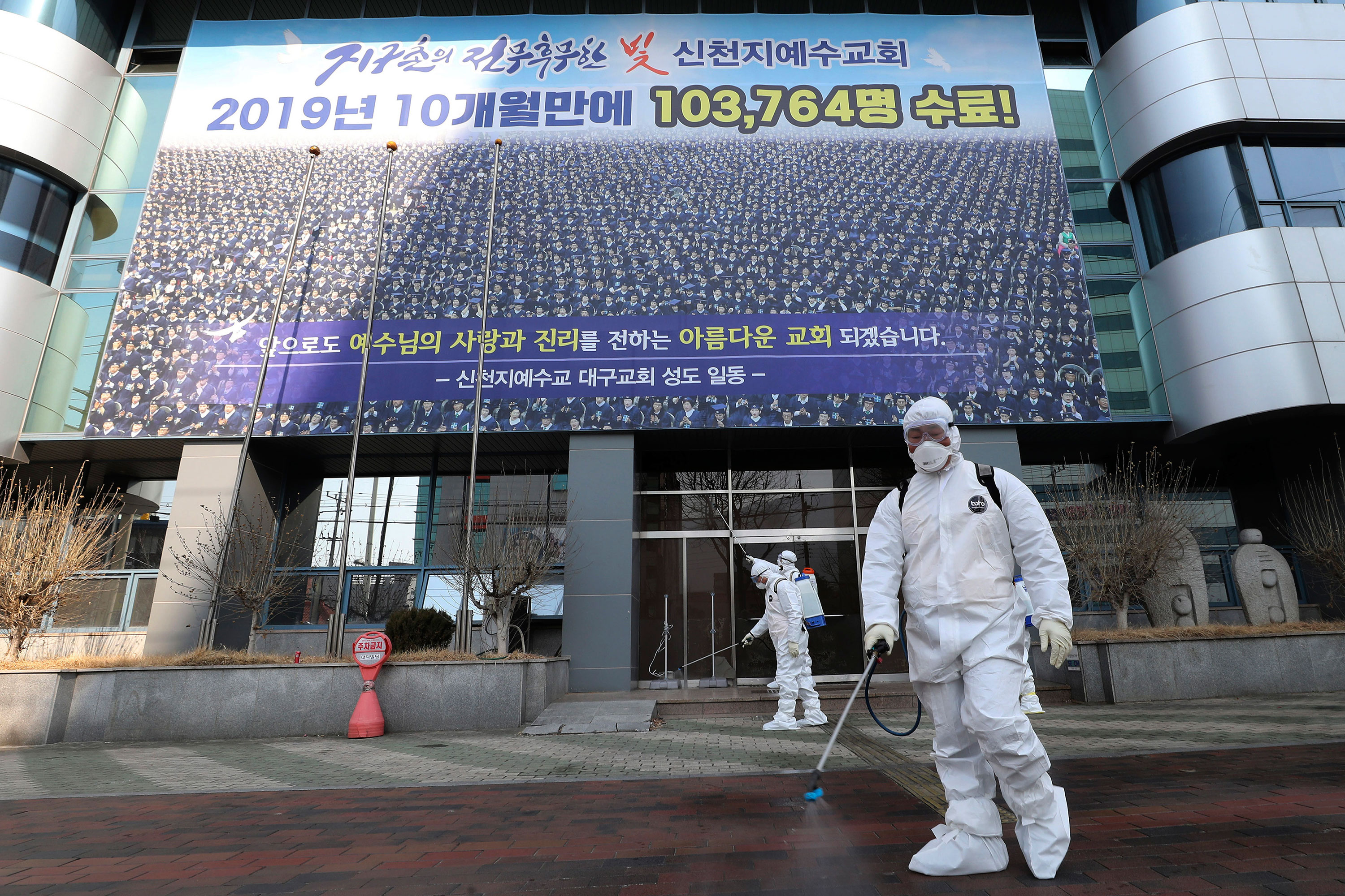 Workers spray disinfectant in front of the Shincheonji building in Daegu, South Korea, on February 21.