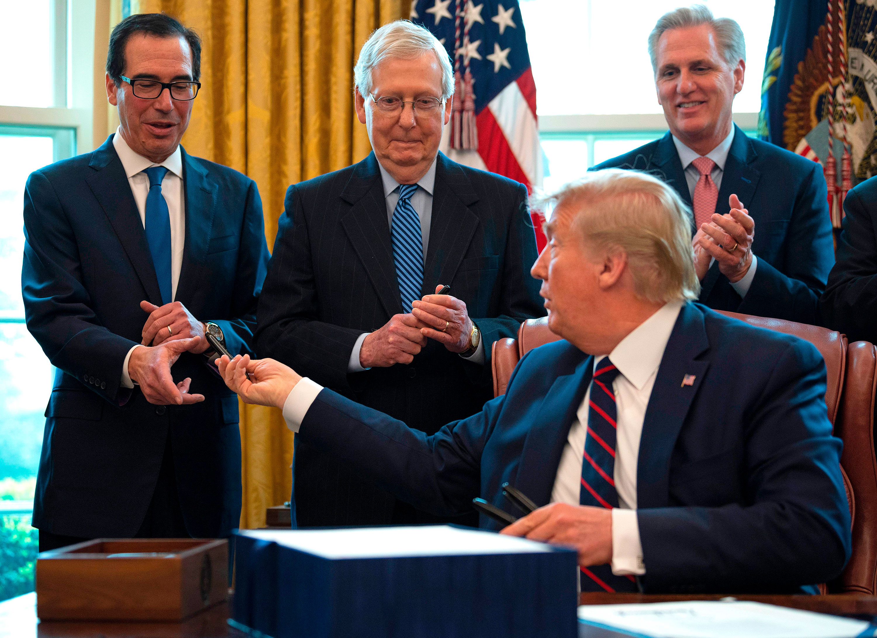 President Donald Trump hands out pens to Treasury Secretary Steven Mnuchin, left, and Sen. Mitch McConnell, center, after signing the CARES act, a $2 trillion rescue package to provide economic relief amid the coronavirus outbreak, on March 27.