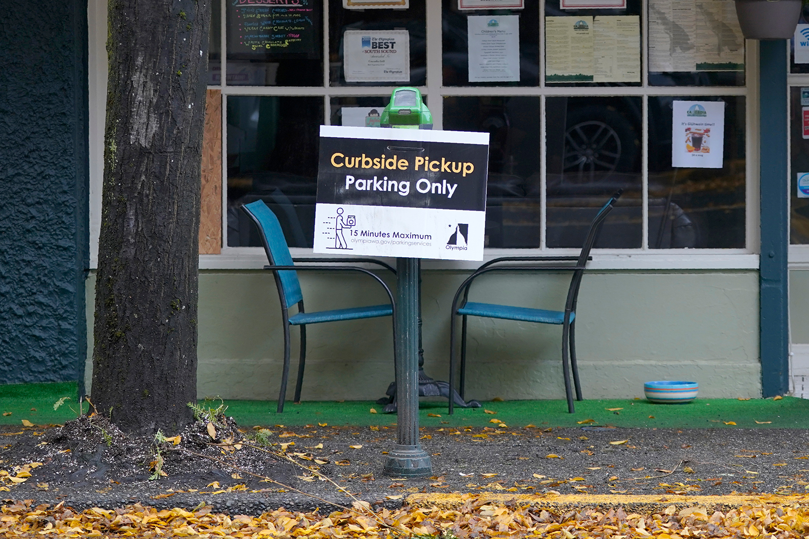A sign for curbside pickup is shown outside the Cascadia Grill, in downtown Olympia, Washington, on November 15.