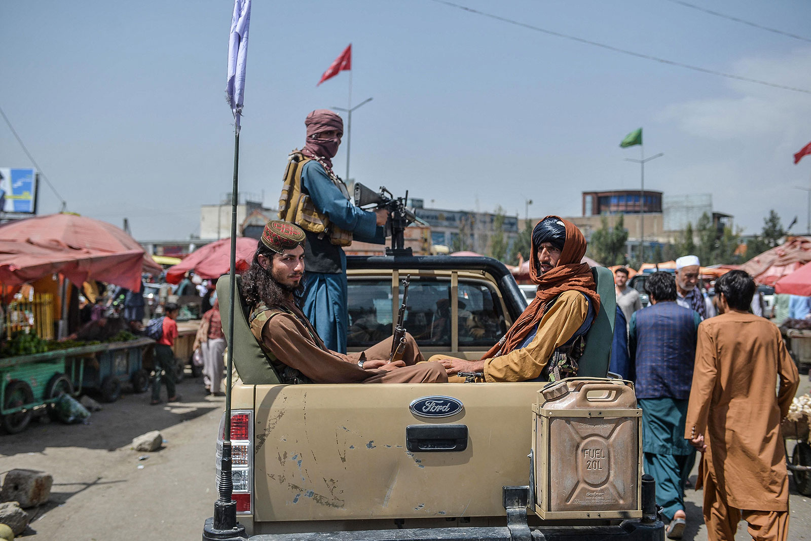 Taliban fighters drive around a market in Kabul on August 17.