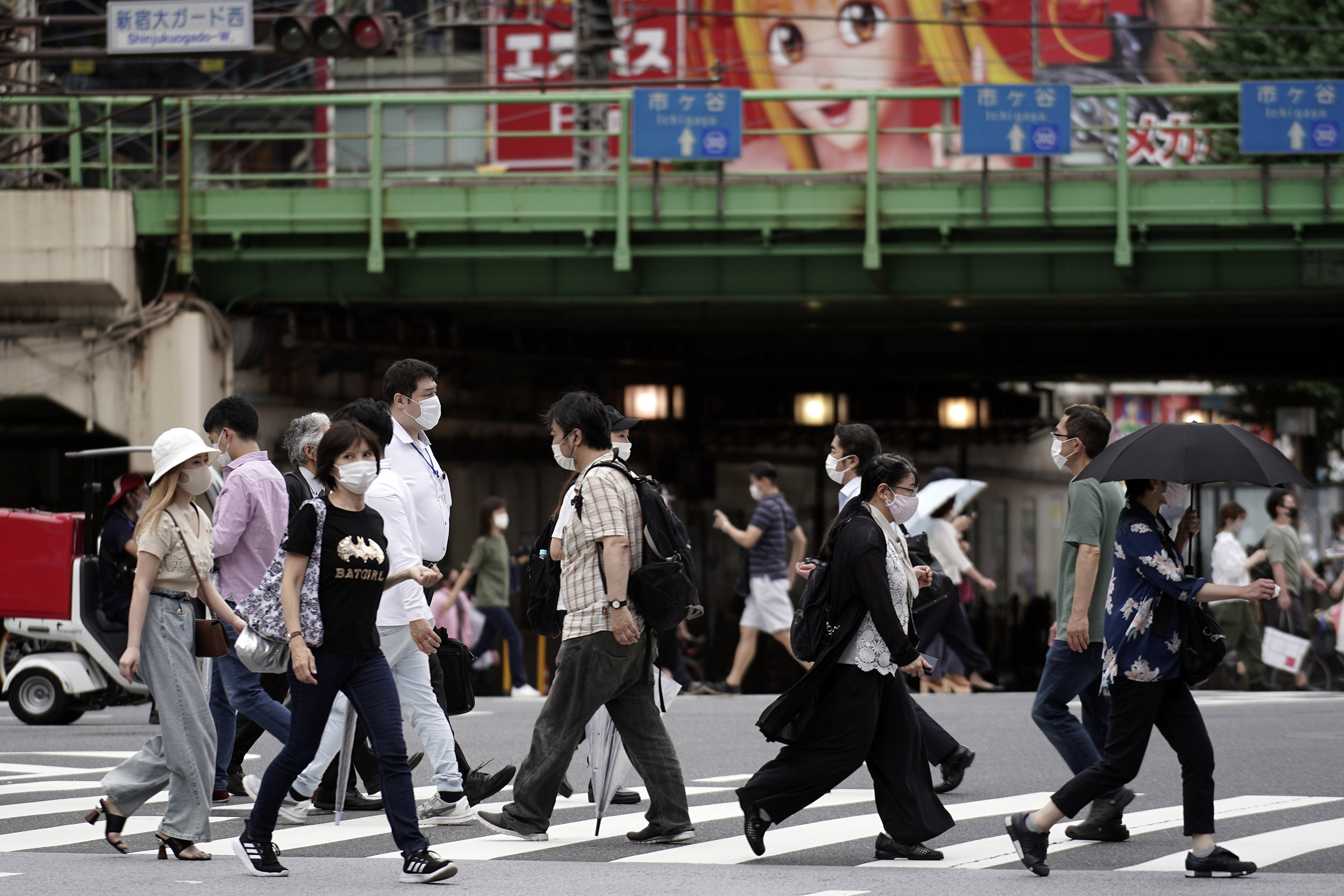 Pedestrians wear protective face masks to help curb the spread of the coronavirus while walking on Friday, July 10, in Tokyo.