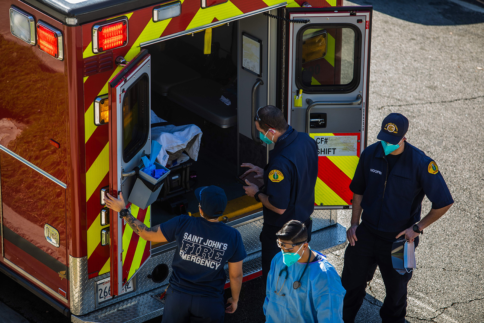After administering oxygen, County of Los Angeles paramedics load a potential Covid-19 patient in the ambulance before transporting him to a hospital in Hawthorne, California on December 29, 2020.