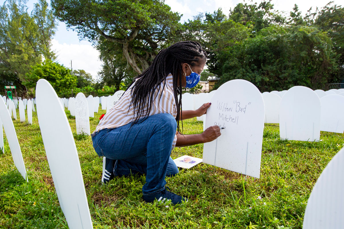 A Miami-Dade County resident creates a symbolic tombstone for a relative at a memorial cemetery for those lost to Covid-19 in Liberty City, Florida on November 24.