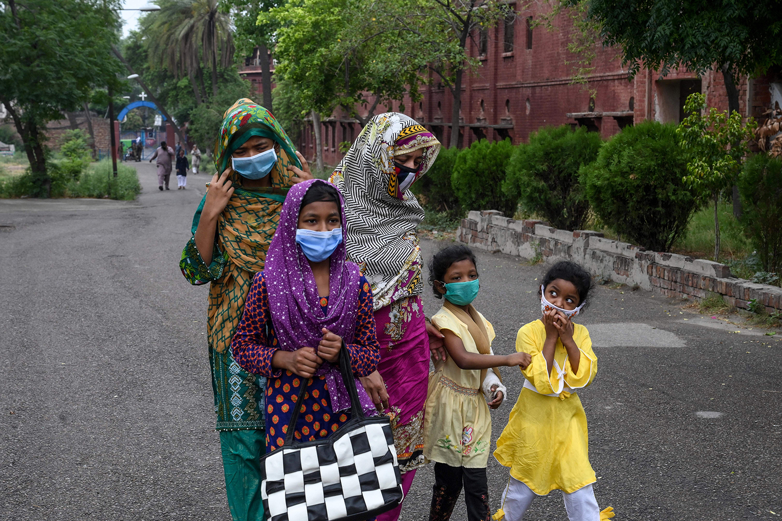 A Catholic family wearing face masks arrives to attend Sunday prayers at the Mary Immaculate Church in Lahore, Pakistan on June 7.