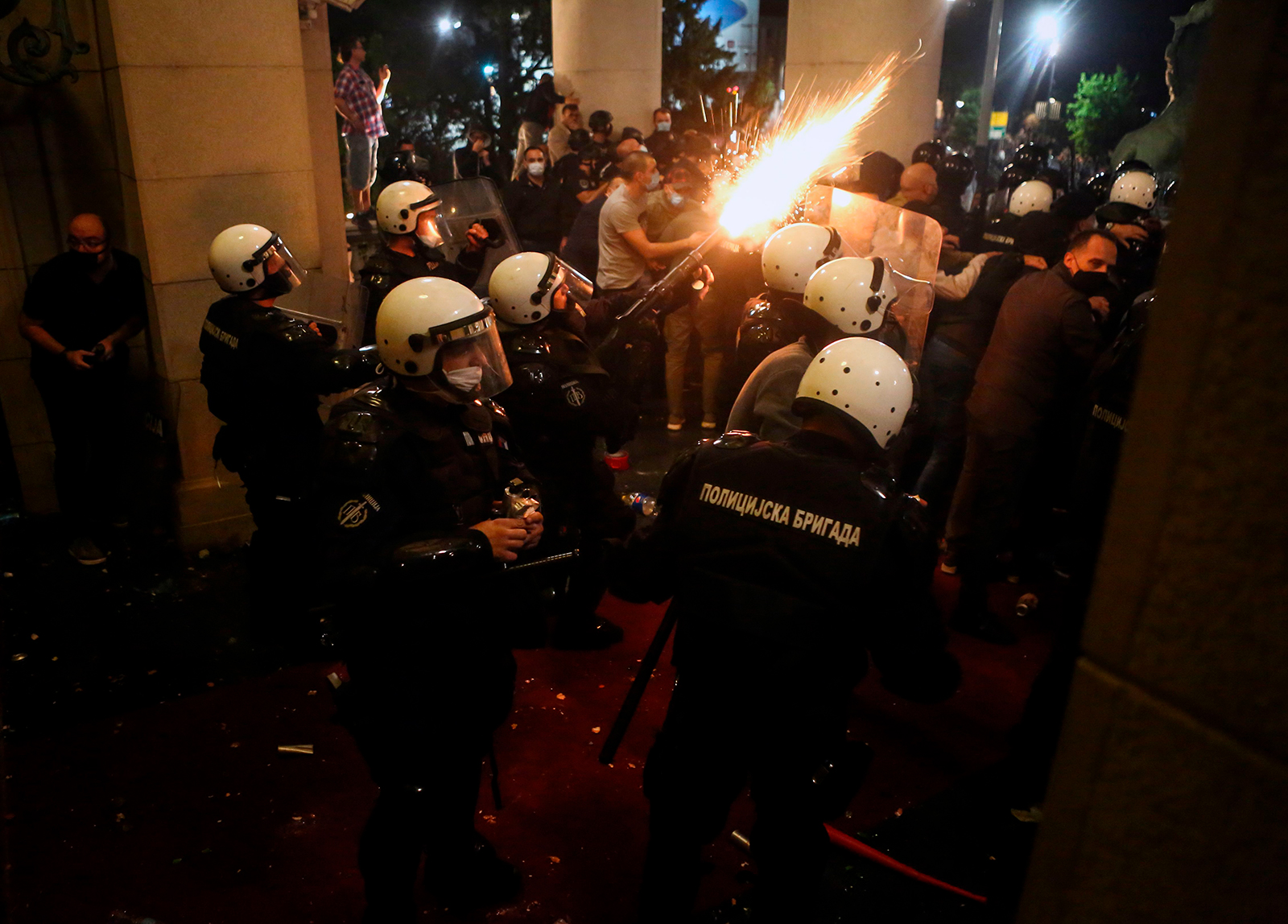 Protesters scuffle with police in front of the National Assembly building in Belgrade, on July 7,  as Serbian police fired tear gas to disperse thousands of protesters angry at the return of a weekend coronavirus curfew.