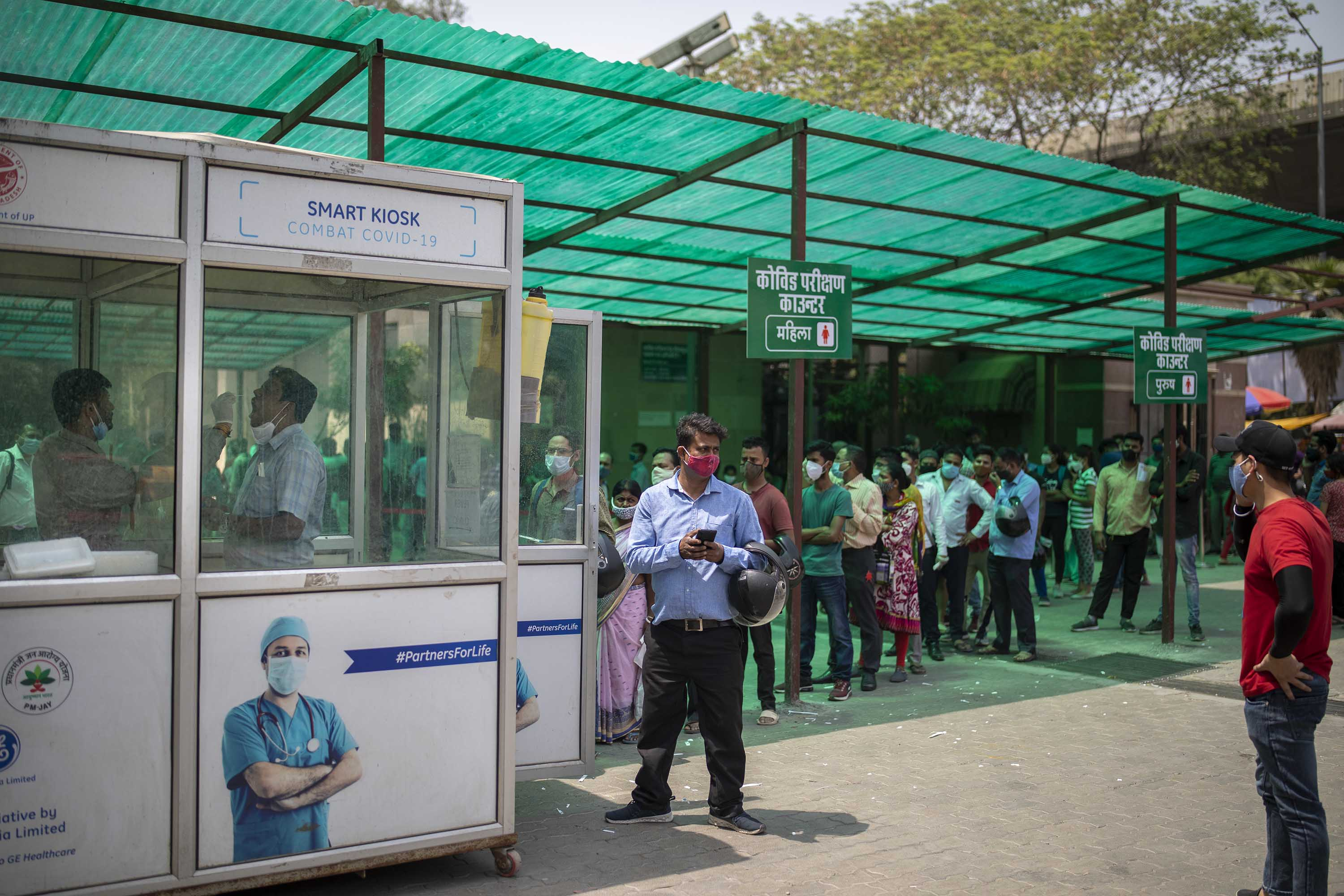 A health worker takes a swab sample to test for Covid-19, as people queue to be tested at a government hospital in Noida, a suburb of New Delhi, India, on Thursday, April 15.