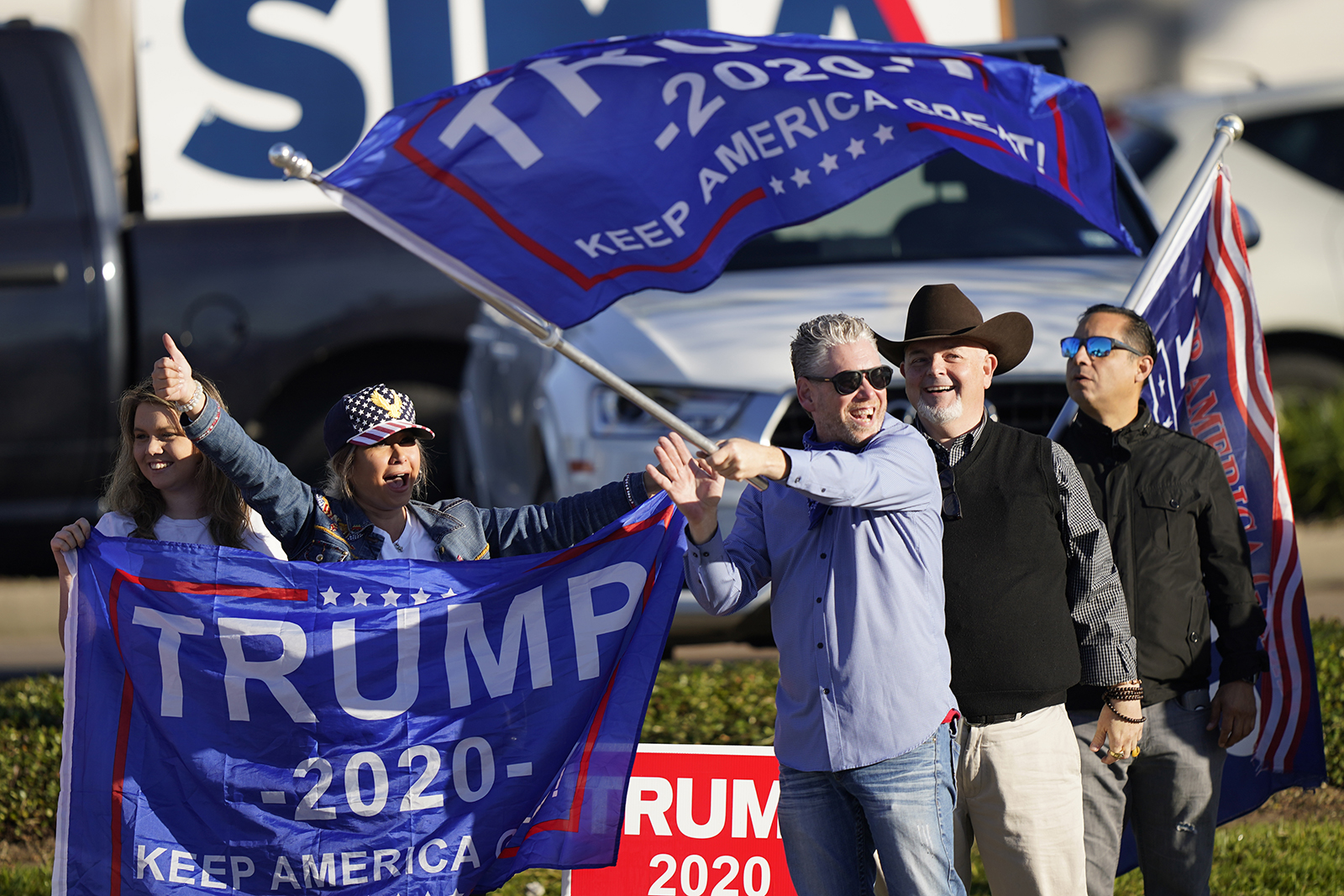 Supporters of President Trump cheer as passing cars honk their horns near a polling location on Election Day, in Houston.
