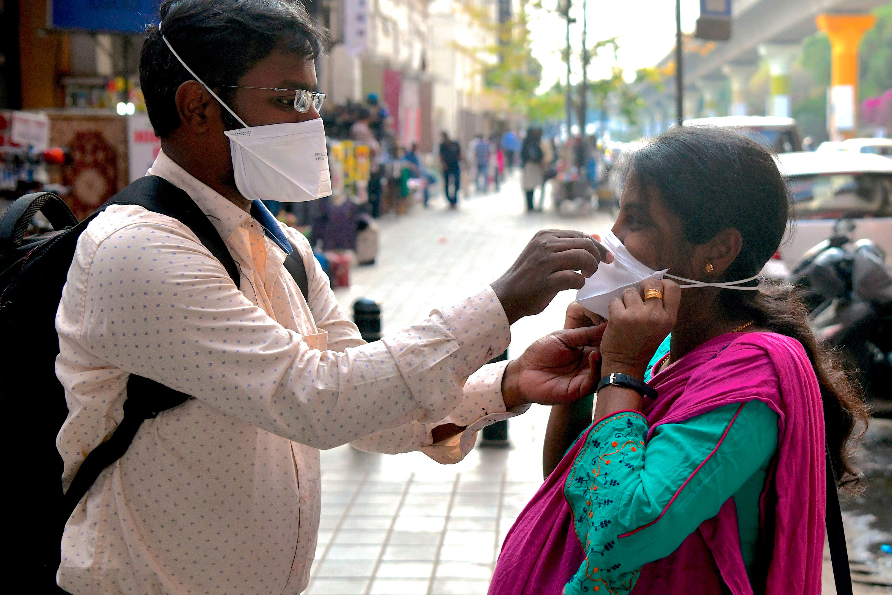 A man helps a woman put on a face mask outside of a metro station in Bangalore, India on March 5.
