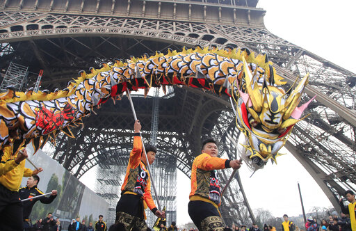People dance with costumes to mark the Chinese New Year at the Eiffel Tower in Paris on Saturday.