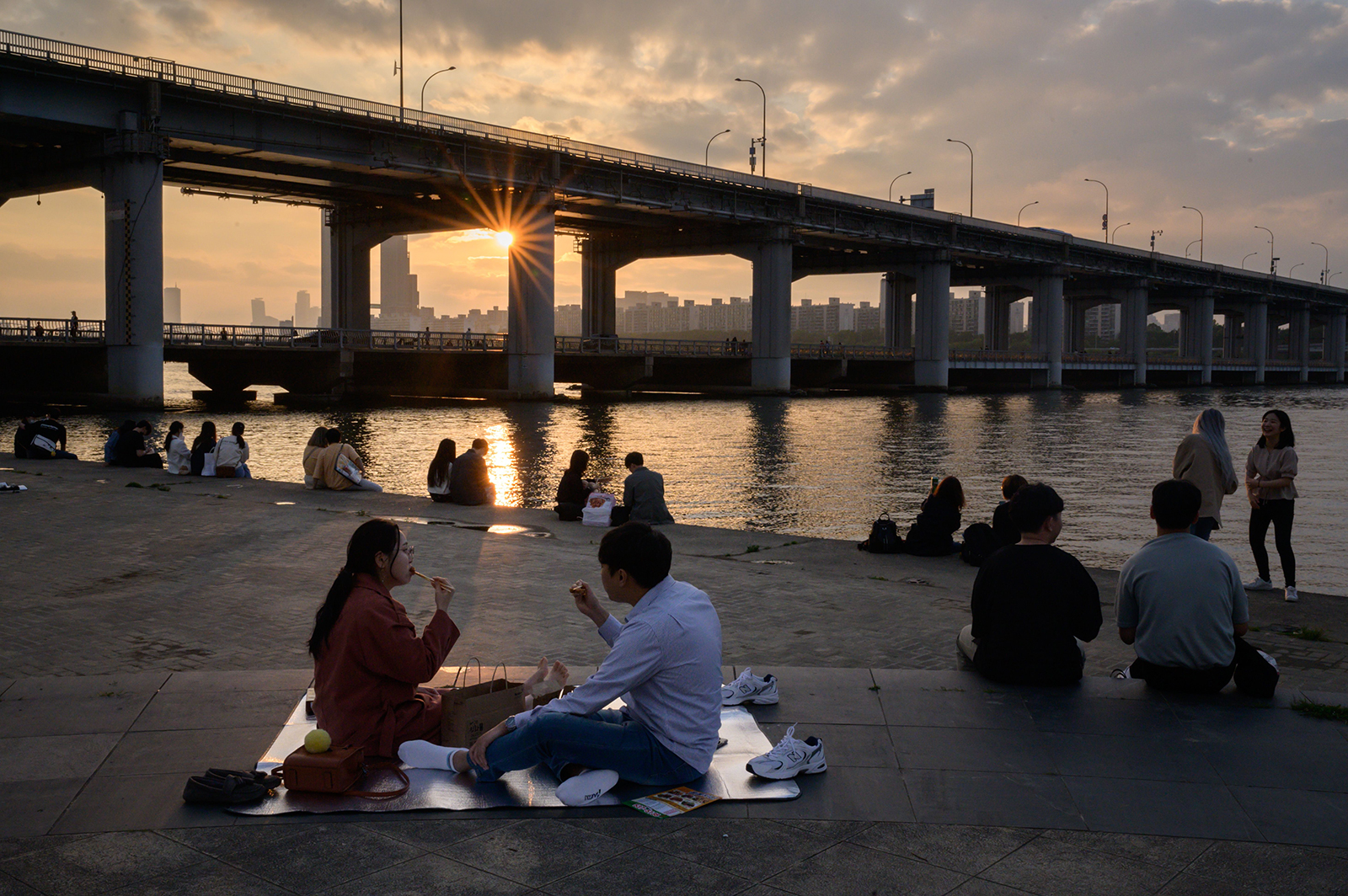 People sit before the city skyline and Han River in Seoul, South Korea, on May 24.