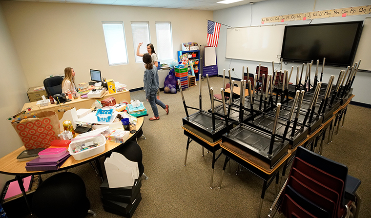 Teachers confer with each other in an empty classroom at Freedom Preparatory Academy on May 18, in Provo, Utah. The school was closed on March 16, along with all other schools in Utah by order of the Utah Governor.
