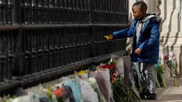 A young boy places flowers on the gate at Buckingham Palace in London.