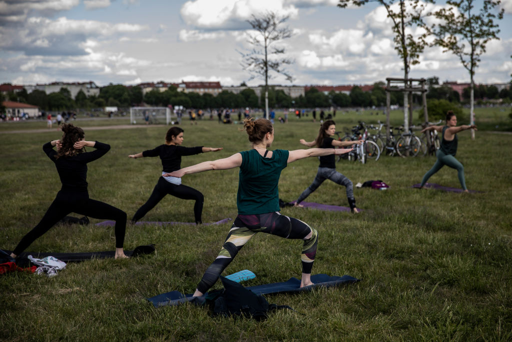 "Group of ""Yoga on the move"" class participants practice Yoga in Tempelhofer Feld on May 17 in Berlin."