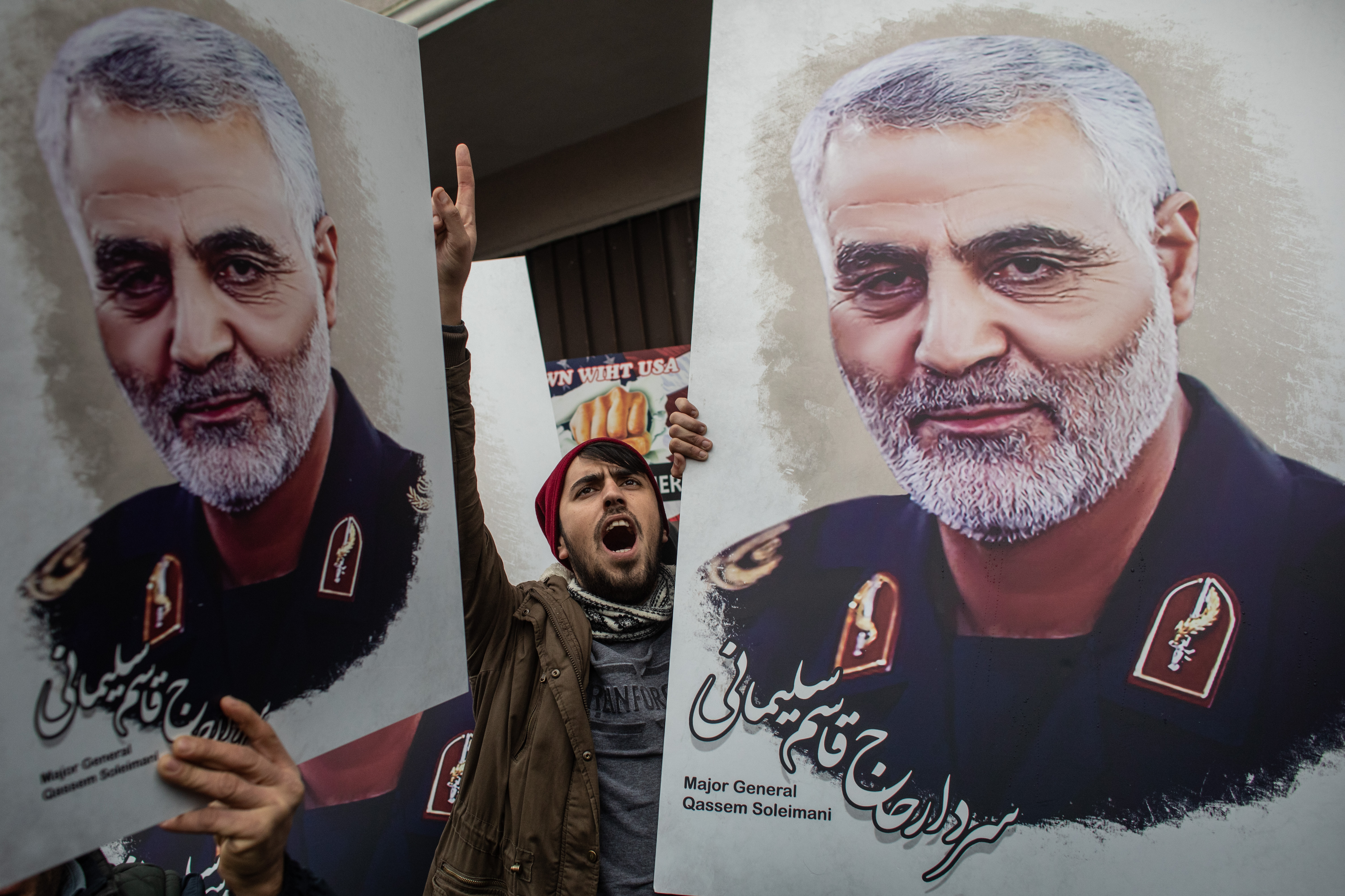 People hold posters showing the portrait of Iranian Revolutionary Guard Major General Qasem Soleimani and chant slogans during a protest outside the US Consulate on Jan. 5 in Istanbul, Turkey.