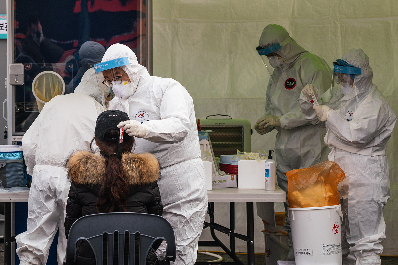 A healthcare worker collects samples from a woman at a temporary Covid-19 testing site in front of Seoul Station in South Korea, on December 18.
