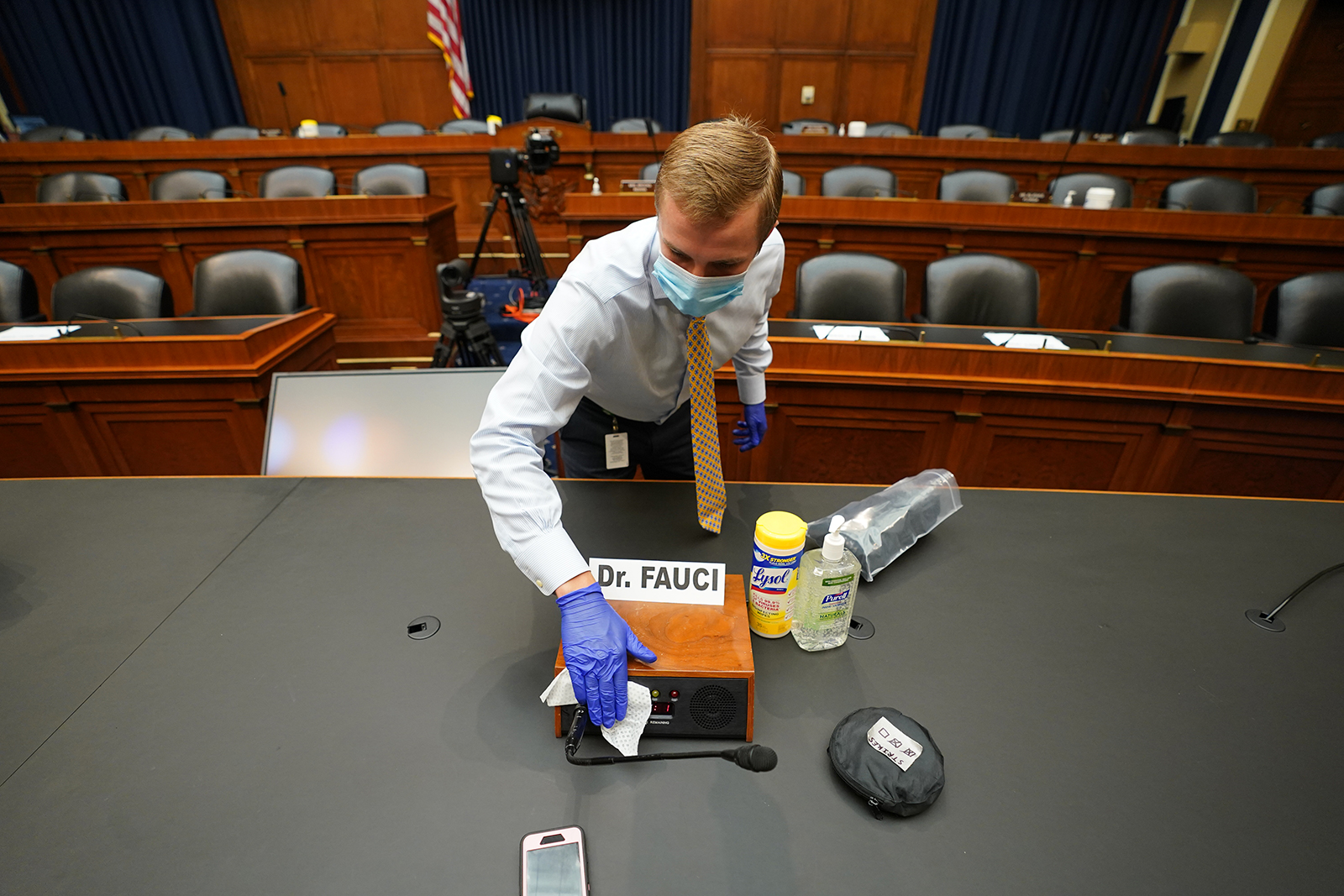 A staff member sanitizes around the name tag for Dr. Anthony Fauci, director of the National Institute for Allergy and Infectious Diseases, before a hearing of the U.S. House Committee on Energy and Commerce on Capitol Hill.