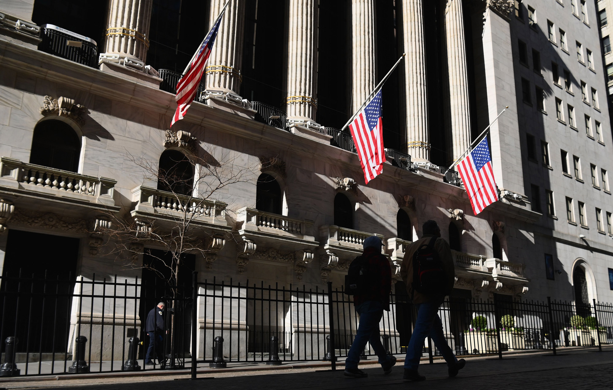 People walk by the New York Stock Exchange at Wall Street on January 12 in New York City.