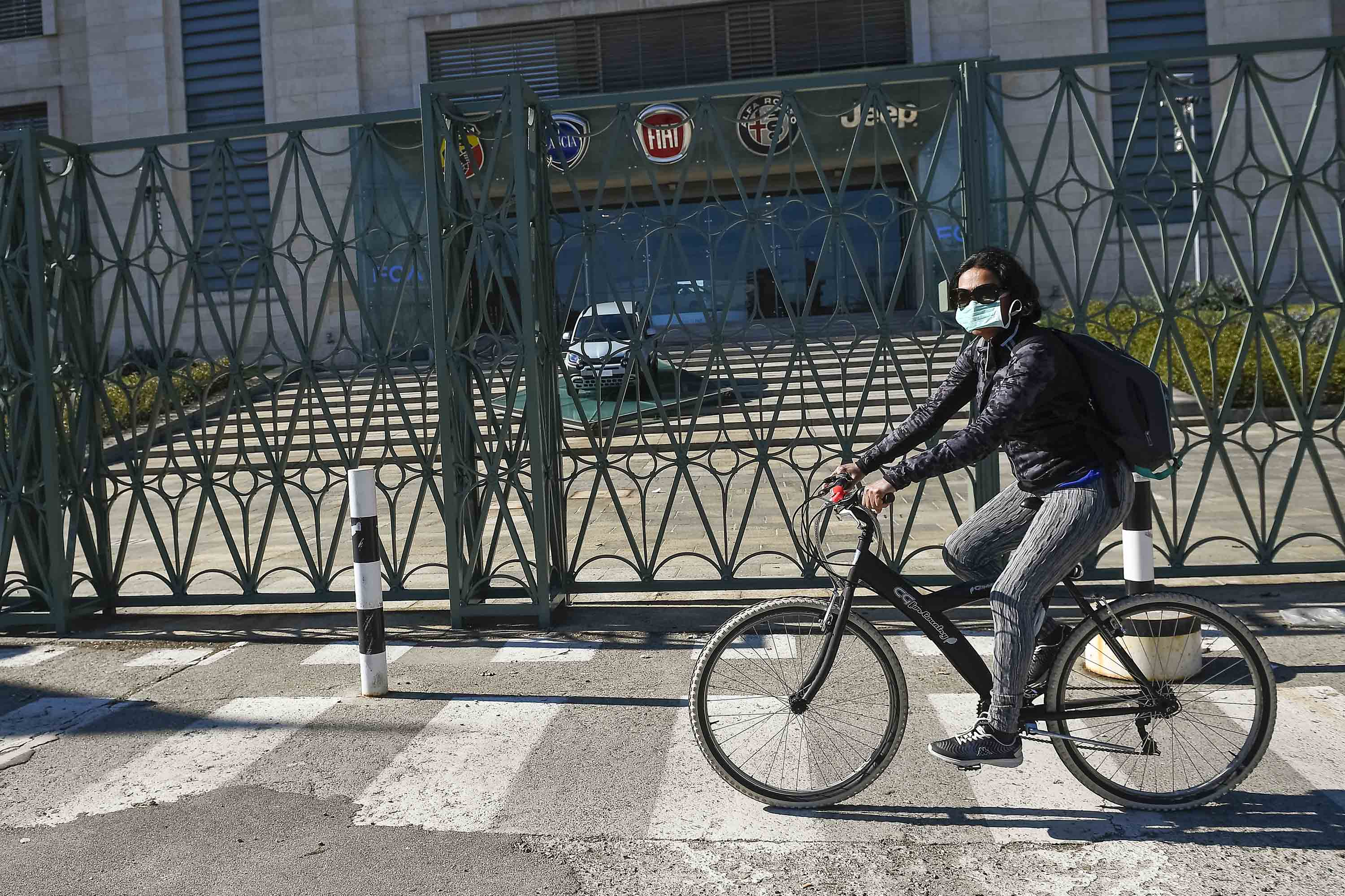A cyclist wearing a respiratory mask rides past the Fiat Mirafiori plant in Turin, Italy, on March 11.