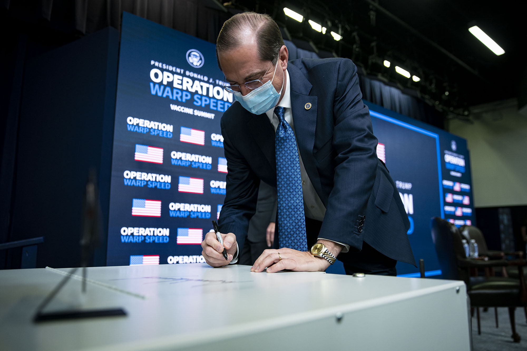 Alex Azar, secretary of Health and Human Services (HHS), signs a Thermo Fisher Scientific Inc. -80C Benchtop Freezer during an Operation Warp Speed vaccine summit at the White House in Washington, D.C., on Tuesday, December 8.