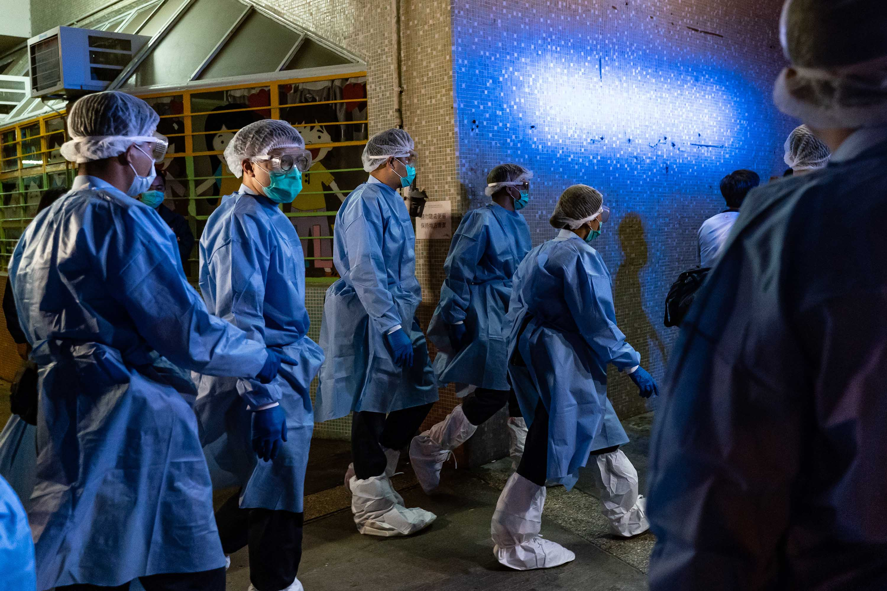 Officials arrive at a public housing building as residents are evacuated from their home to a quarantine center, after multiple infections of the novel coronavirus were detected at a housing estate in Hong Kong on March 14.