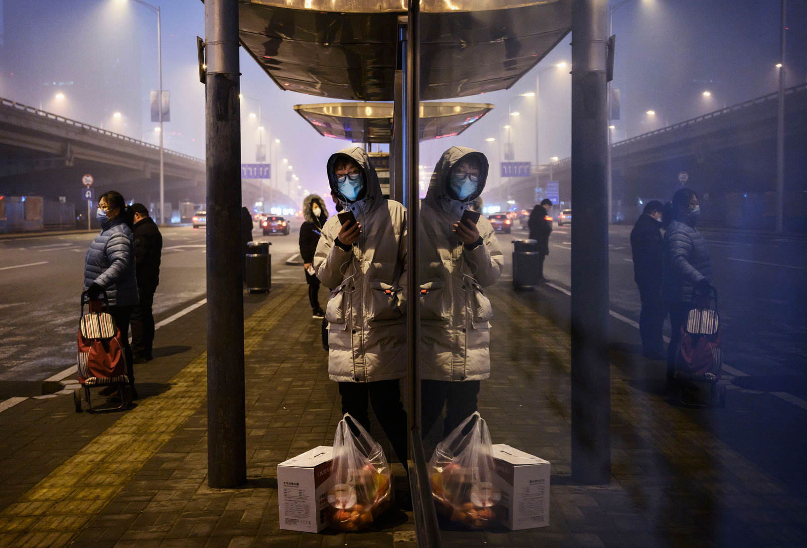 Chinese commuters wear protective masks as they wait for a bus at a usually busy stop on February 13, in Beijing, China.