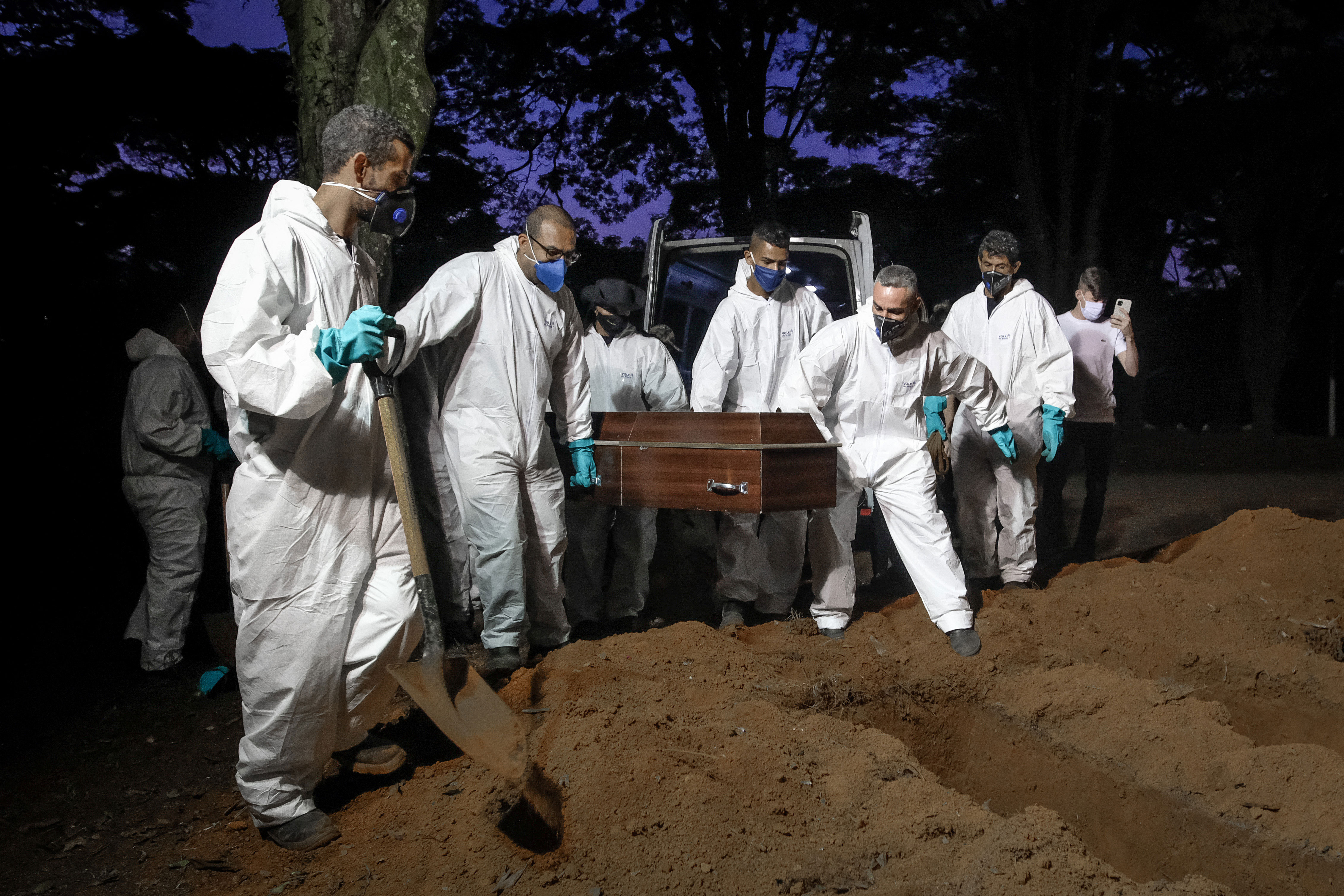 Employees of the Vila Formosa cemetery carry a coffin to bury a person who died of Covid-19 in São Paulo, Brazil, on April 2.