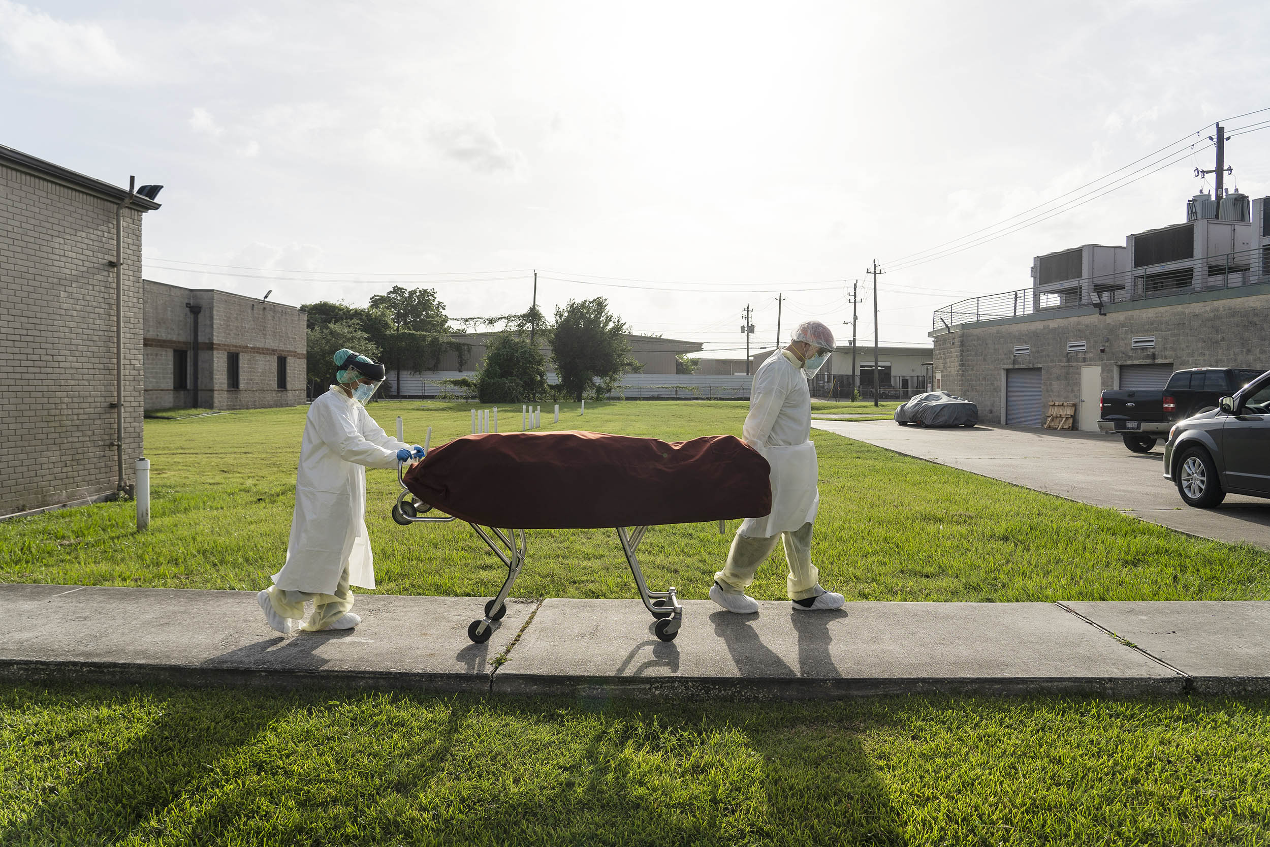 Medical staff wearing full PPE push a stretcher with a deceased patient to a car outside of the Covid-19 intensive care unit at the United Memorial Medical Center on June 30, in Houston, Texas.