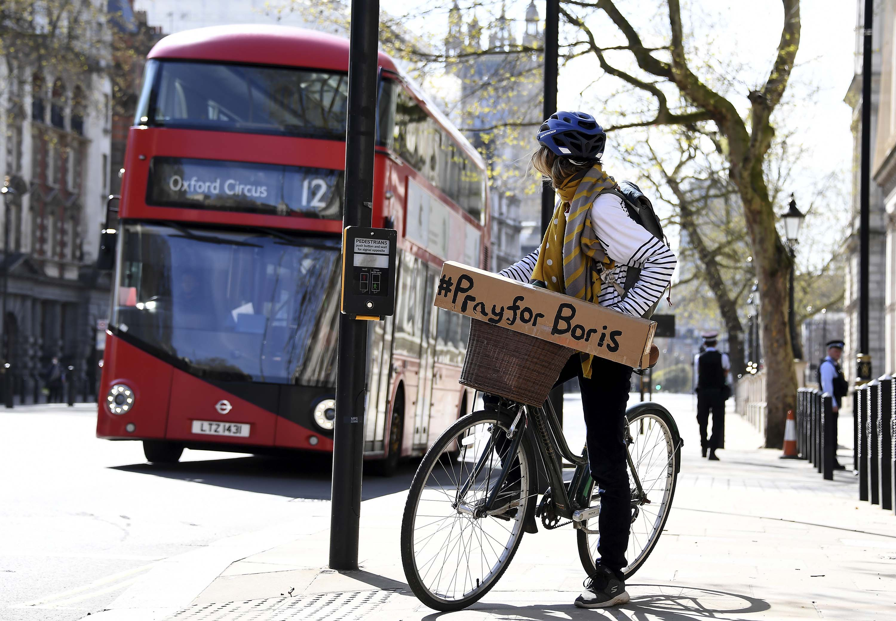 A woman on a bicycle displays a sign of support for British Prime Minister Boris Johnson, who remains in hospital in London, on April 7.