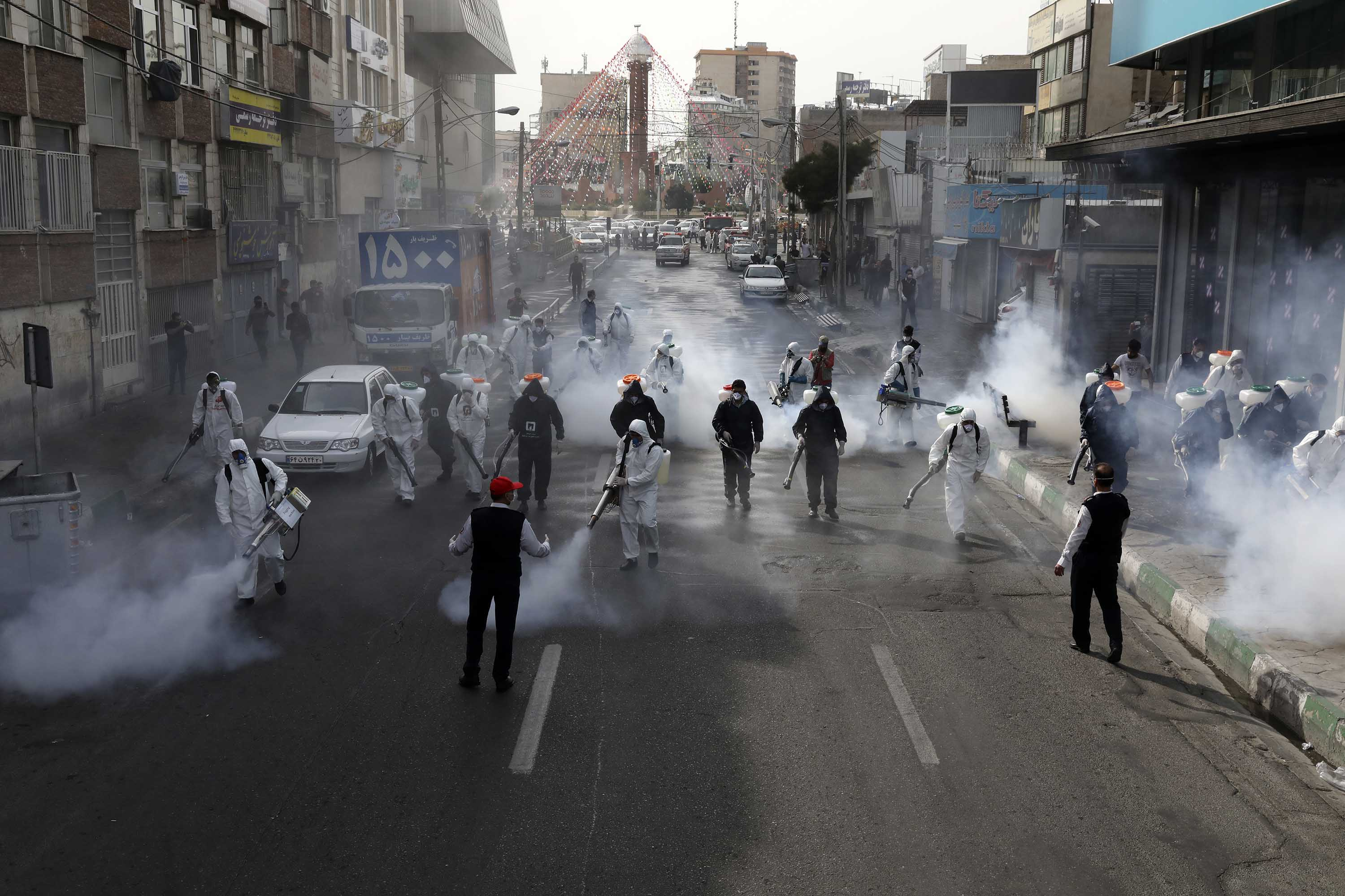 Firefighters disinfect a street against the coronavirus in Tehran, Iran, on March 13.