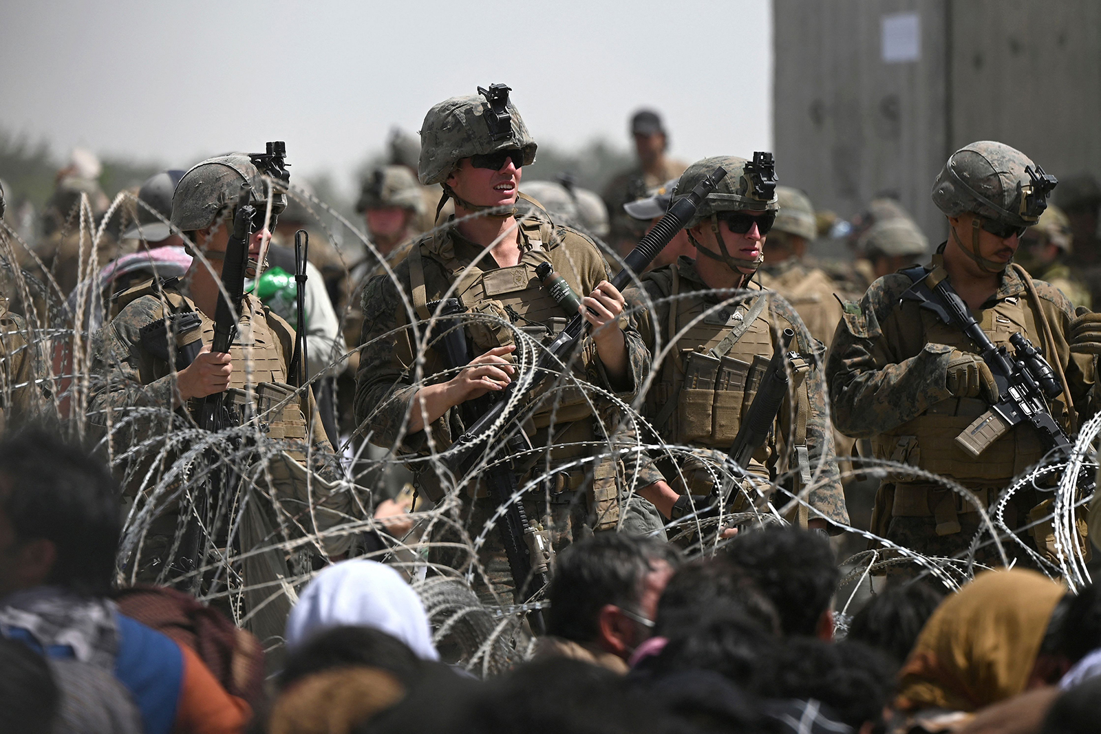 US soldiers stand guard behind barbed wire as Afghans sit on a roadside near the military part of the airport in Kabul on August 20.