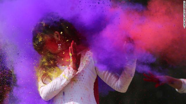 Indian college girls throw colored powder to one another during Holi festival celebrations in Bhopal in 2018.