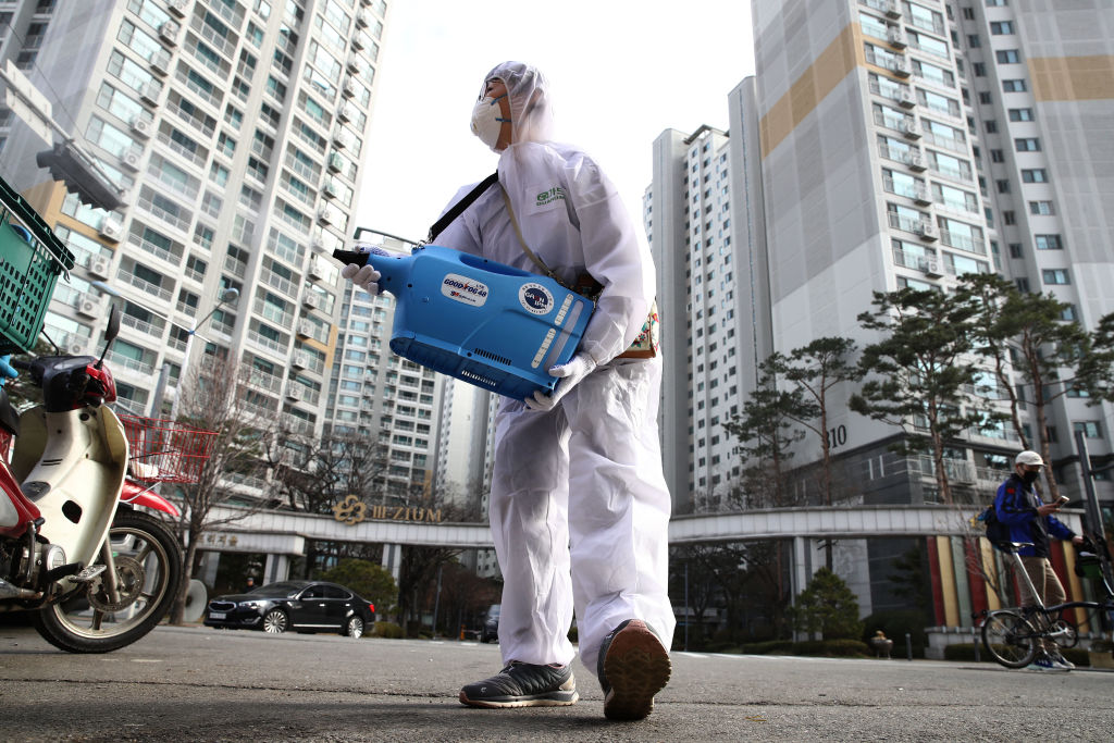 A worker sprays antiseptic solution against the coronavirus in Seoul yesterday.