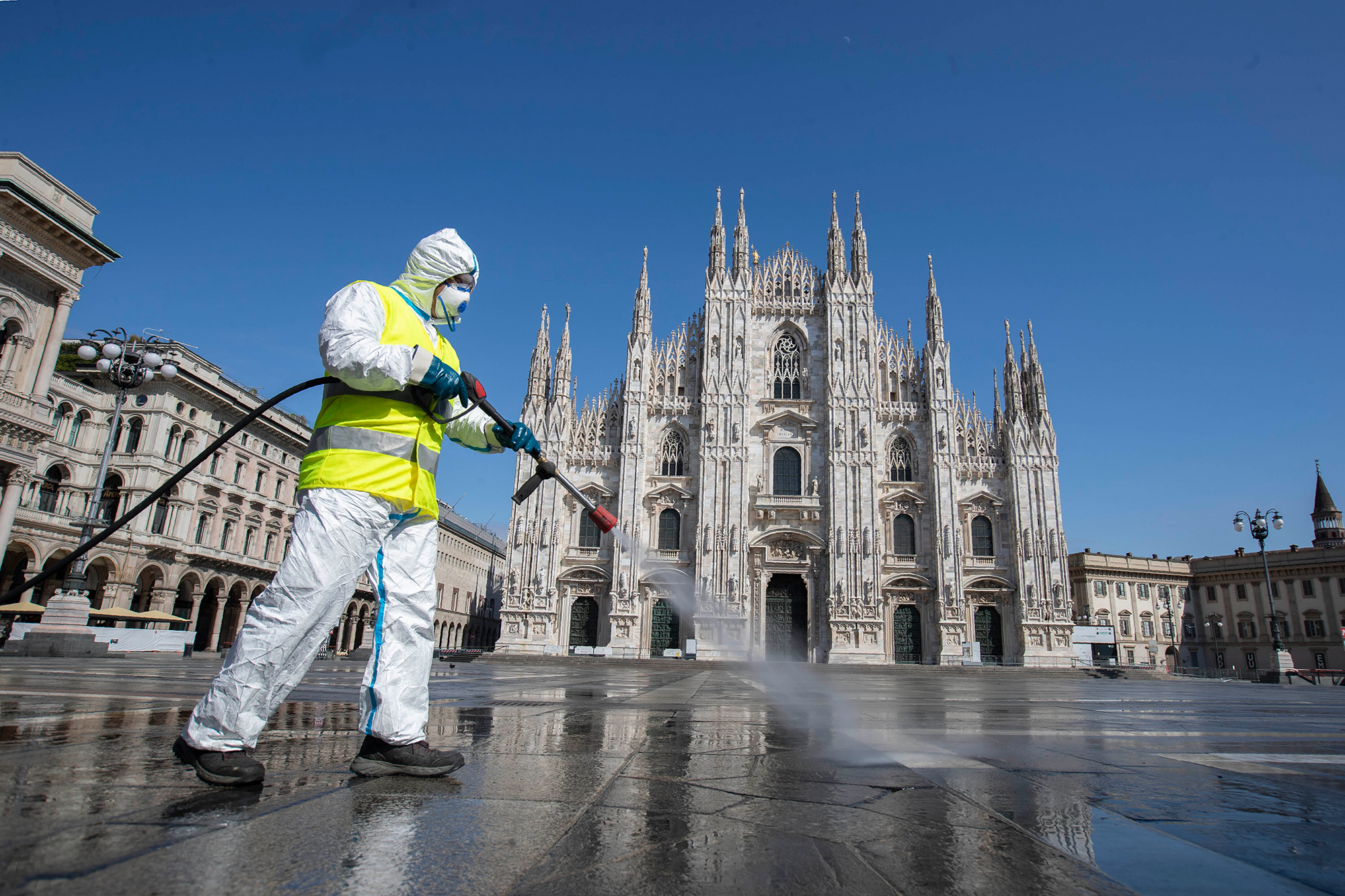 A worker sprays disinfectant to sanitize Duomo square in Milan, Italy, on Tuesday, March 31.