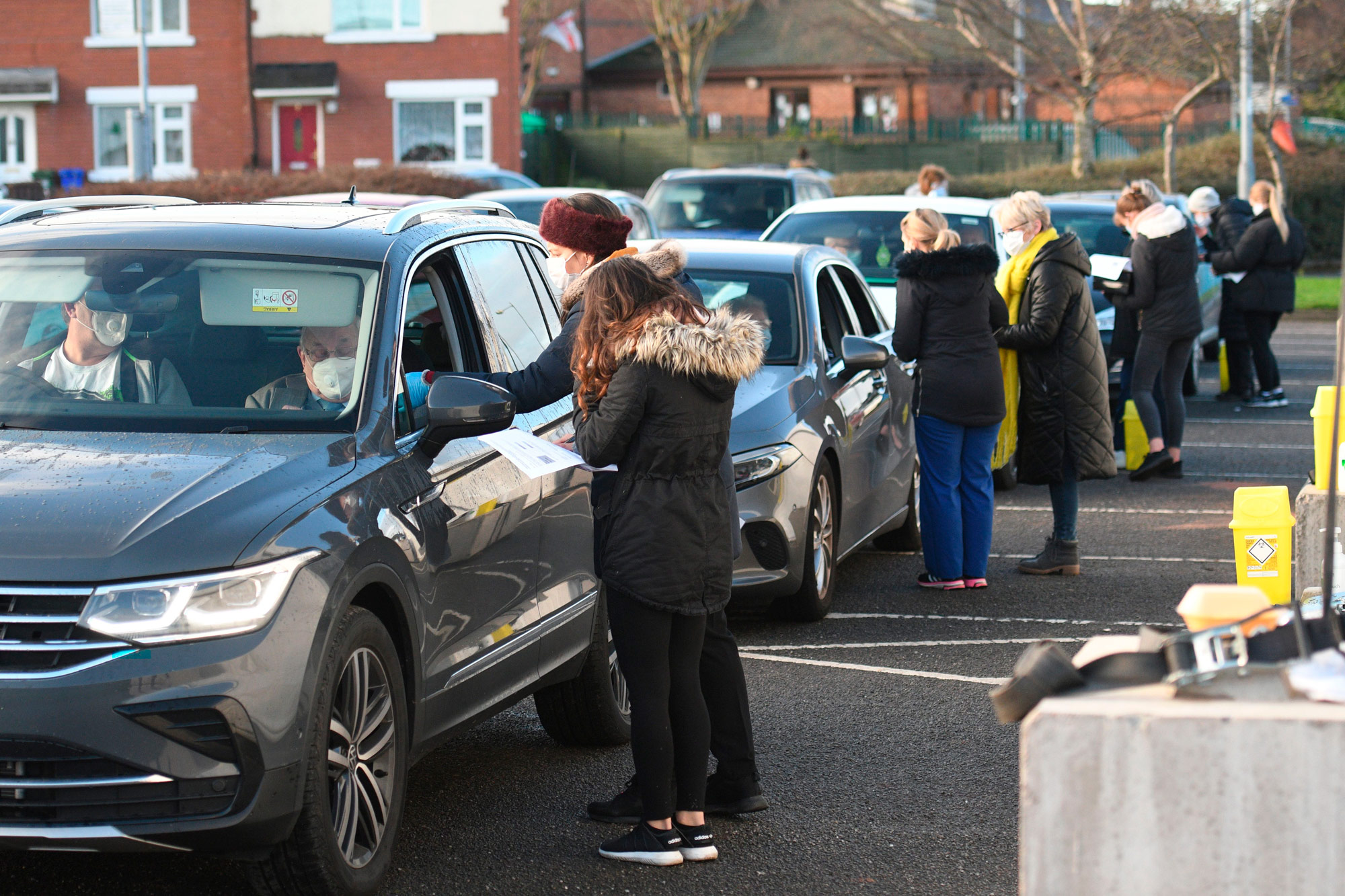 Staff deliver injections of the first dose of the Pfizer-BioNTech Covid-19 vaccine to patients at a drive-in vaccination center in Hyde, Greater Manchester, England on December 17.