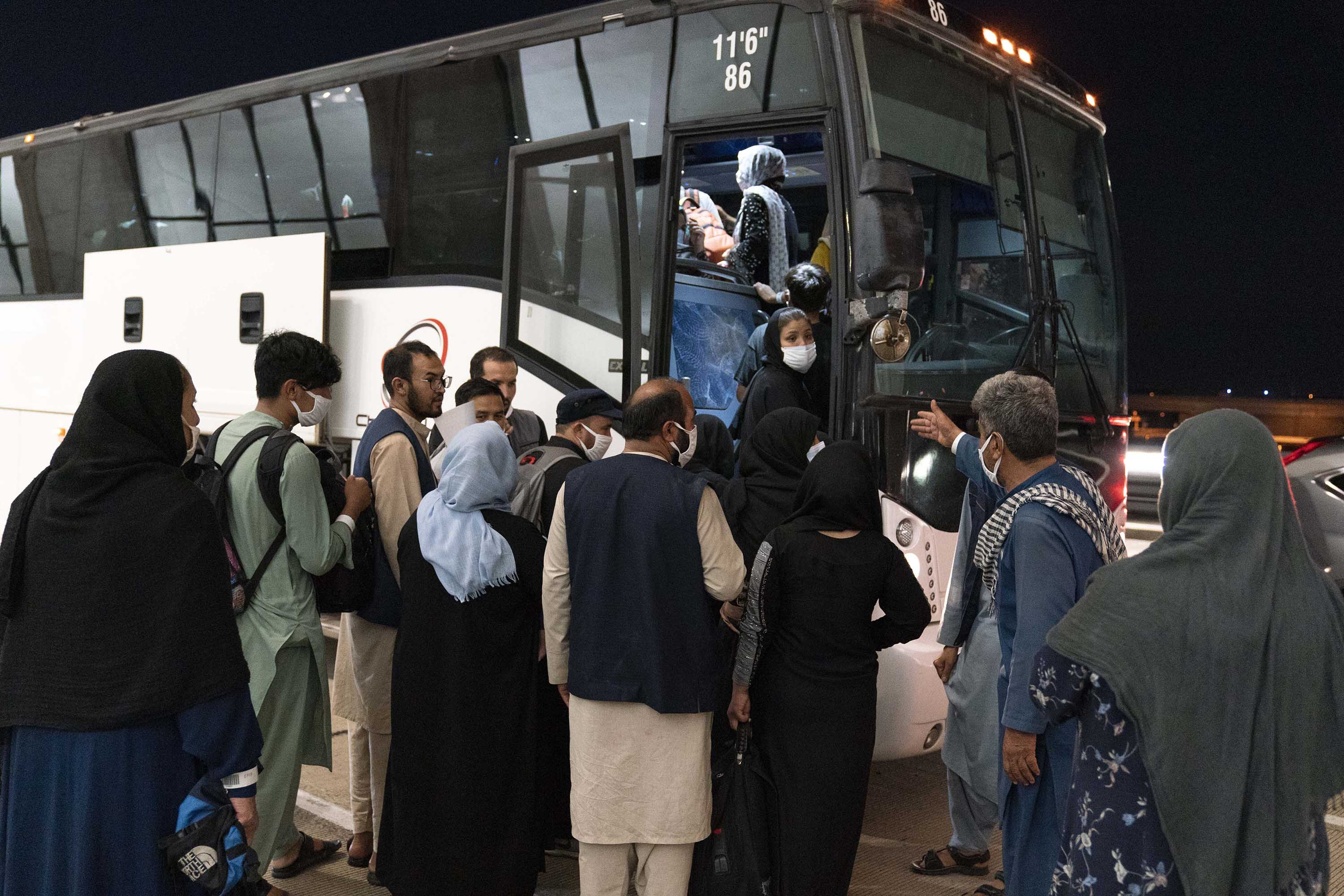 Evacuees from Kabul, Afghanistan board a bus after arriving at Washington Dulles International Airport in Chantilly, Virginia, on Saturday, August 21.