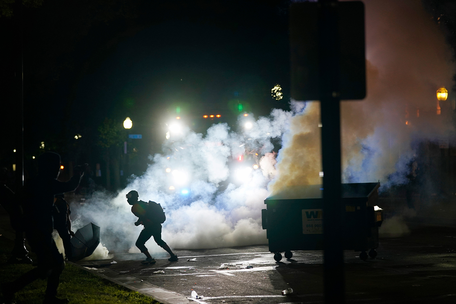 A protester moves away from a smoke canister late Tuesday.