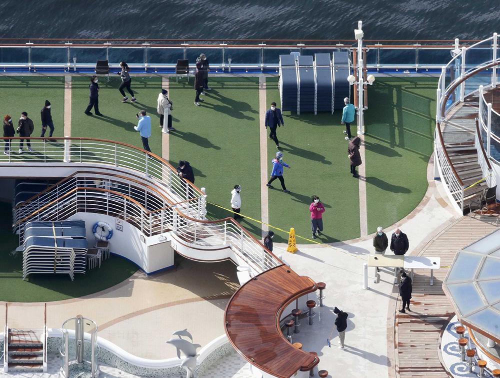 Masked passengers are seen on the deck of the cruise ship Diamond Princess docked at Yokohama Port, near Tokyo, Friday, February 7.