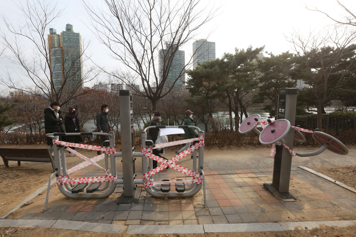 People wearing face masks walk by taped public sports facilities at a park in Seoul, South Korea on January 3.
