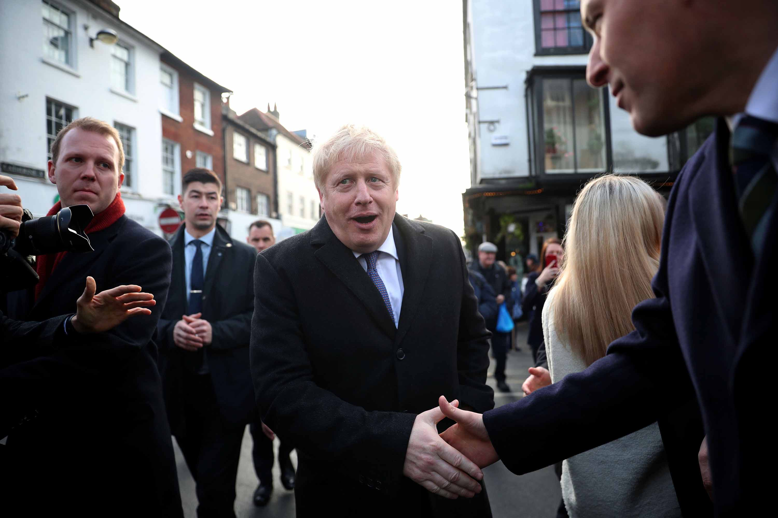 Boris Johnson greets people as he visits a Christmas market during a campaign event in Salisbury, England on Tuesday. Photo: Hannah McKay/AFP via Getty Images