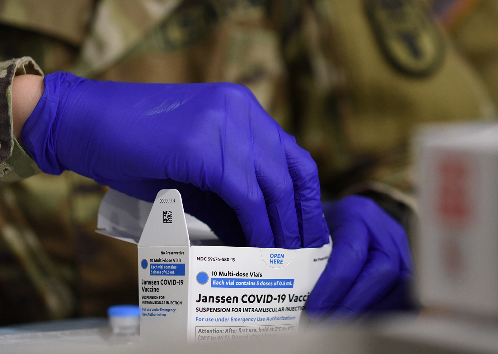 An Army medic removes vials of Johnson & Johnson Covid-19 vaccine from a box at a vaccination site in Orlando, Florida, on April 10.