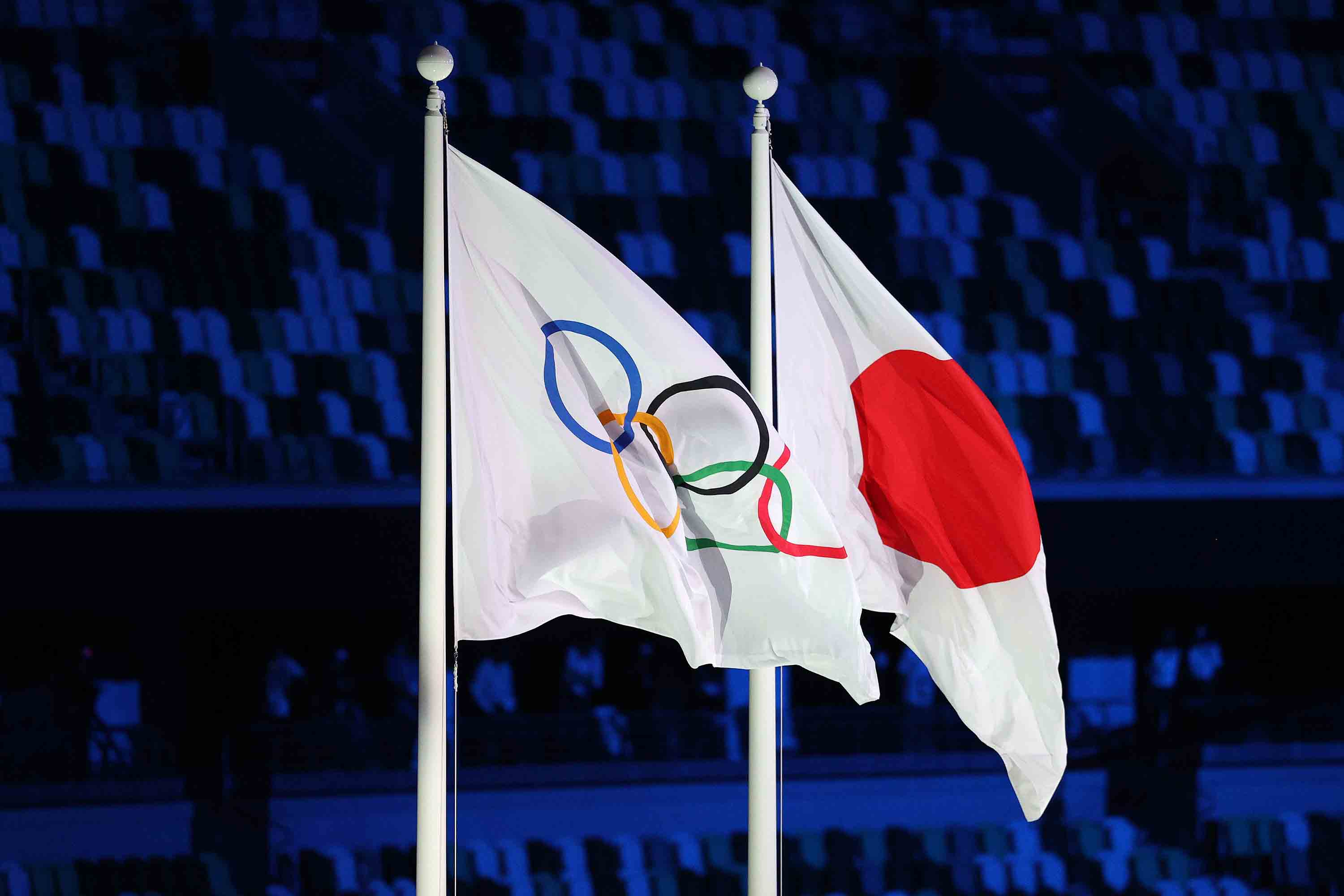 The Olympic flag is raised alongside the Japanese flag during the Opening Ceremony.