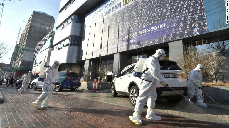 Workers from a disinfection service company sanitize a street in front of a branch of the Shincheonji religious group in Daegu, South Korea, on February 19.