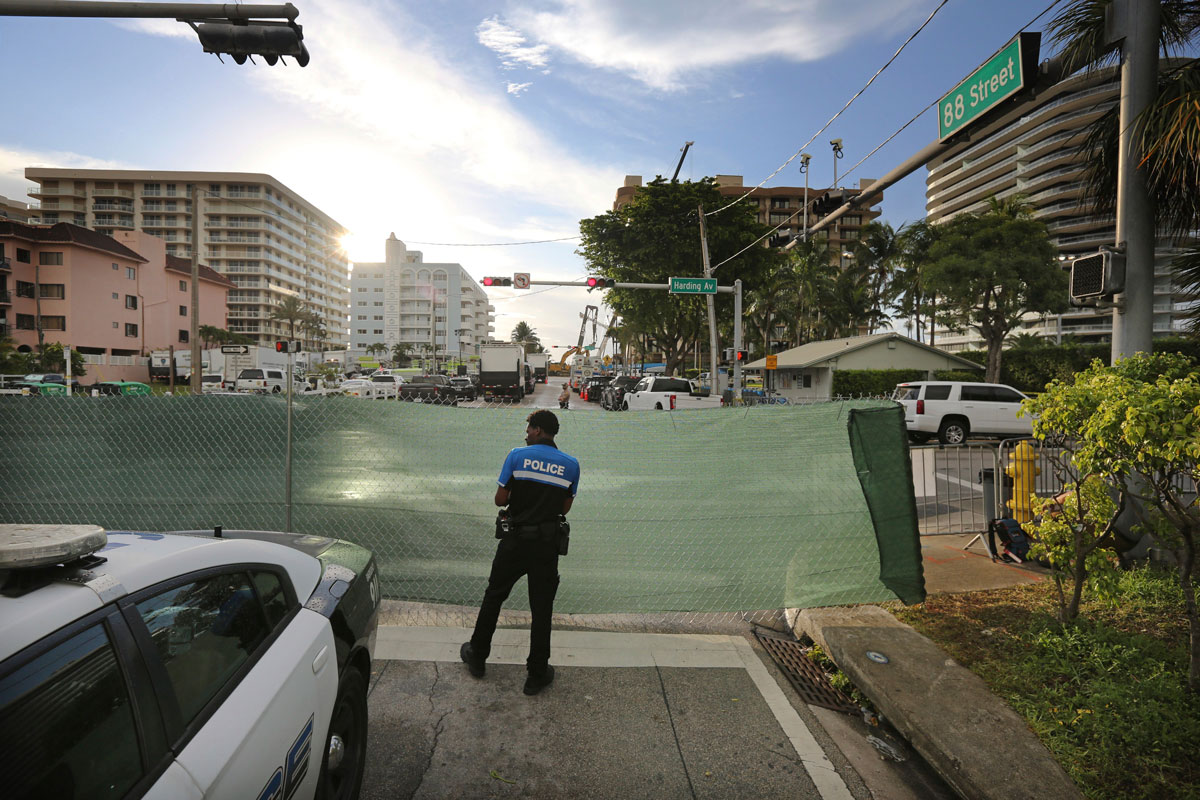 A police officer stands guard at the intersection of 88th Street and Harding Avenue near the Champlain Towers South Condo in Surfside, Miami on June 28.