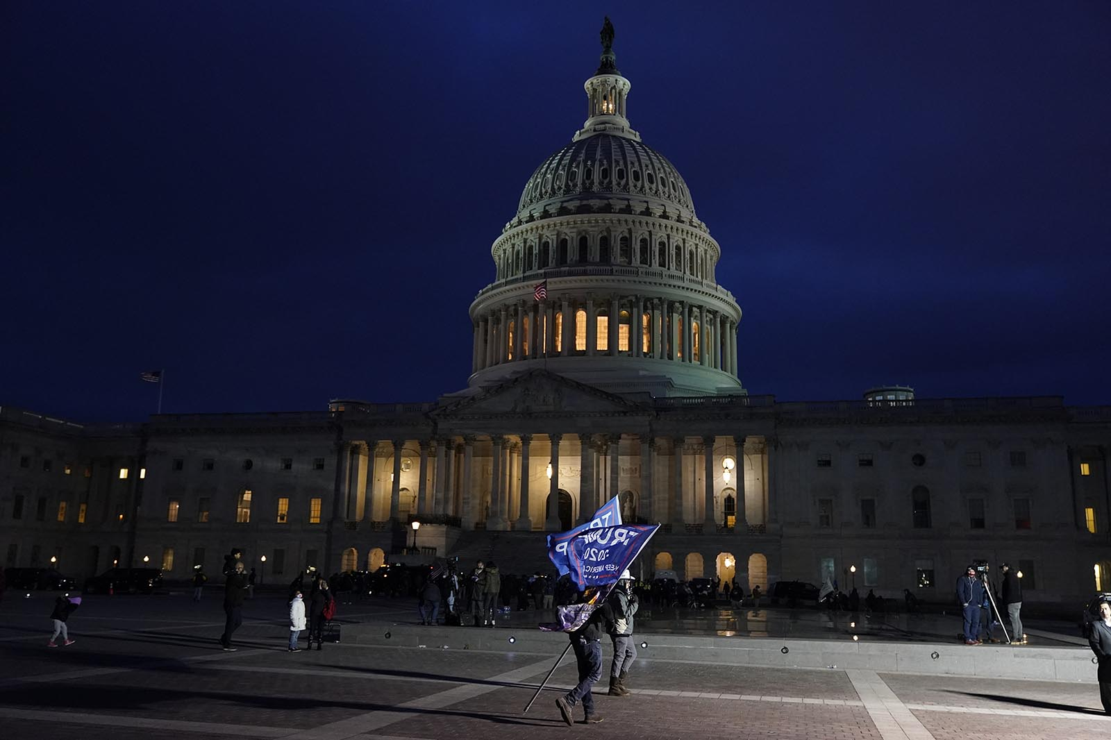 A supporter of President Donald Trump holds Trump flags stand outside the U.S. Capitol on Wednesday, January 6, in Washington.
