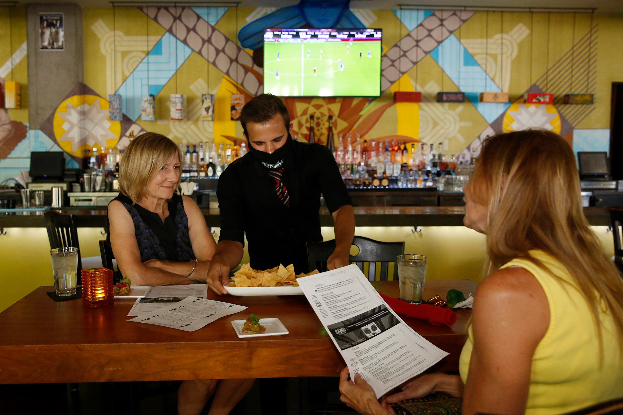 Jorge Hernandez serves a plate of chips to customers at the Tequila Museo Mayahuel restaurant in Sacramento, California, on July 1.