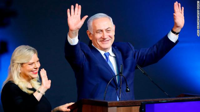 Israeli Prime Minister Benjamin Netanyahu greets supporters, alongside his wife Sara, at his Likud party headquarters on election night.