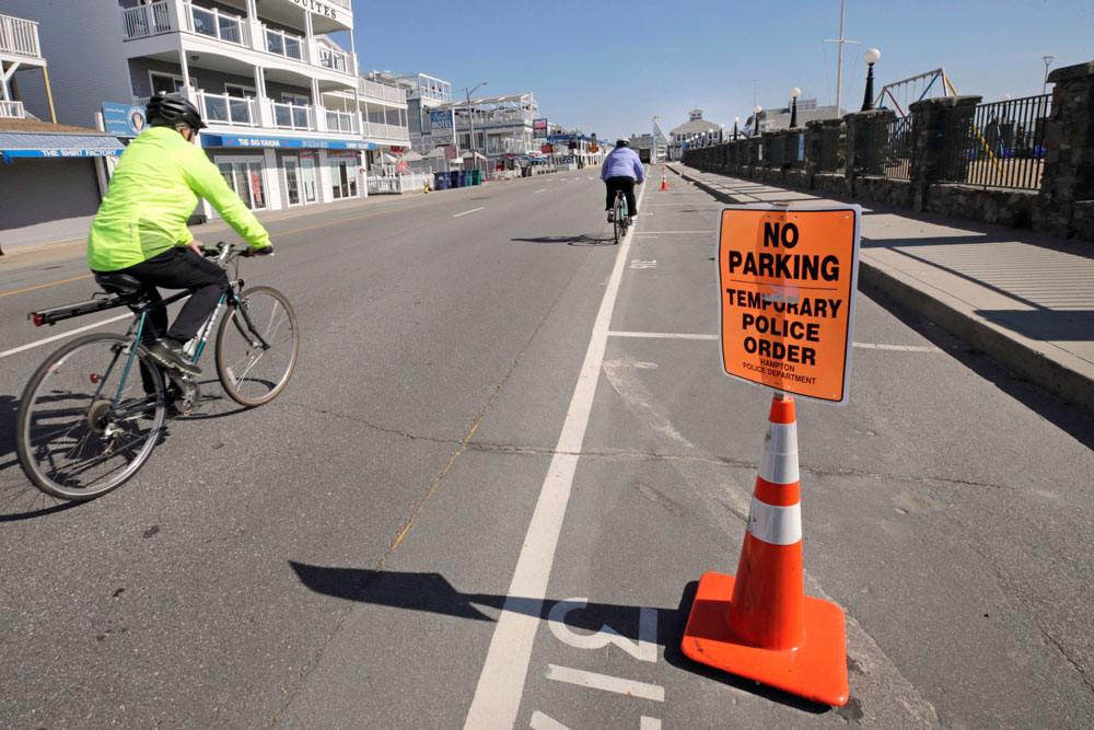 Two cyclists pass empty parking spots adjacent to Hampton Beach in Hampton, New Hampshire, on Thursday, May 21.
