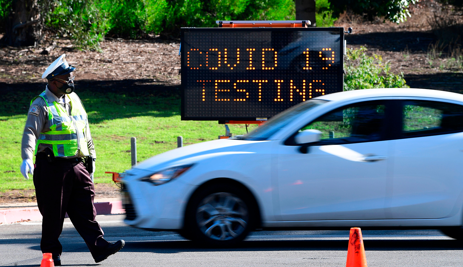 A traffic officer directs drivers as people arrive and depart from the Covid-19 testing venue at Dodger Stadium in Los Angeles, on Thursday, November 12.
